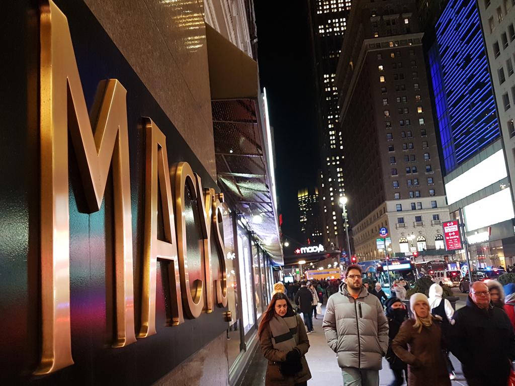 Letrero de bronce de Macys Herald Square Manhattan, gente caminando noche de invierno. Foto de Andrea Hoare Madrid