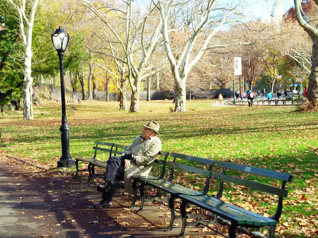 Elegante señor mayor tomando sol en otoño en una banca de Central Park - Foto de Andrea Hoare Madrid