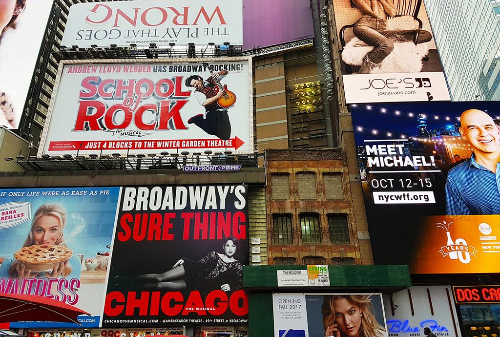 Letreros a musicales de Broadway sobre un edificio en el Distrito de los Teatros - Foto de AHM