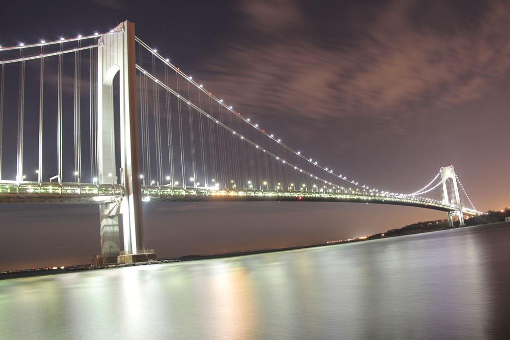 Foto del Puente Verrazano-Narrows de noche visto desde Brooklyn de Violinbd / CC BY-SA (https://creativecommons.org/licenses/by-sa/3.0), vía Wikimedia disponible en https://commons.wikimedia.org/wiki/File:Verrazano-Narrows_Bridge_@_Night_from_Brooklyn.JPG