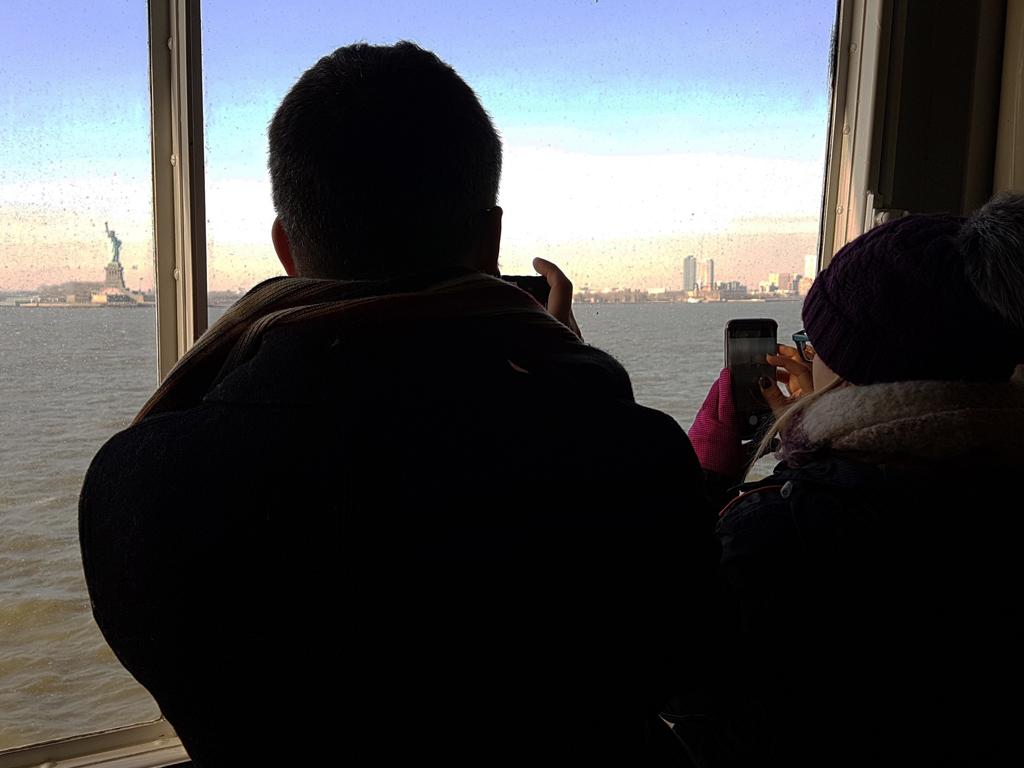 Turistas fotografiando la Estatua de la Libertad desde el ferry anaranjado a Staten Island - Foto de Andrea Hoare Madrid