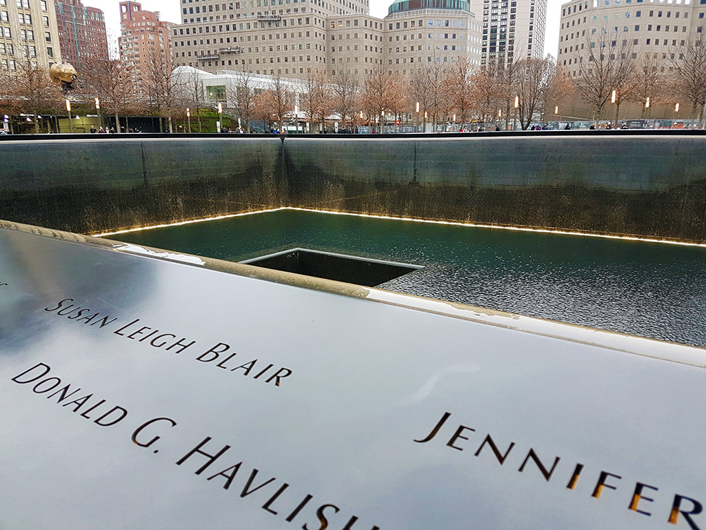 Detalle de algunos nombres de víctimas del atentado de las Torres Gemelas en el borde de una de las piletas del Memorial del WTC - Foto de AHM