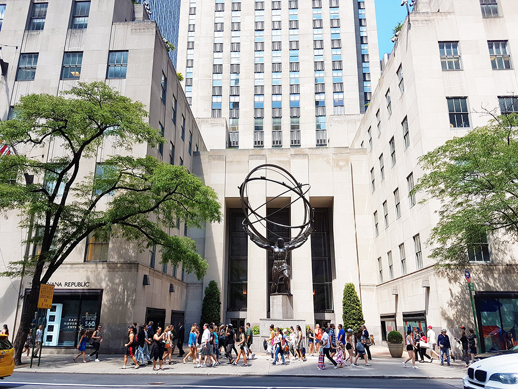 Gente caminando frente a la Estatua del Atlas del Rockefeller Center en la quinta avenida - Foto de AHM