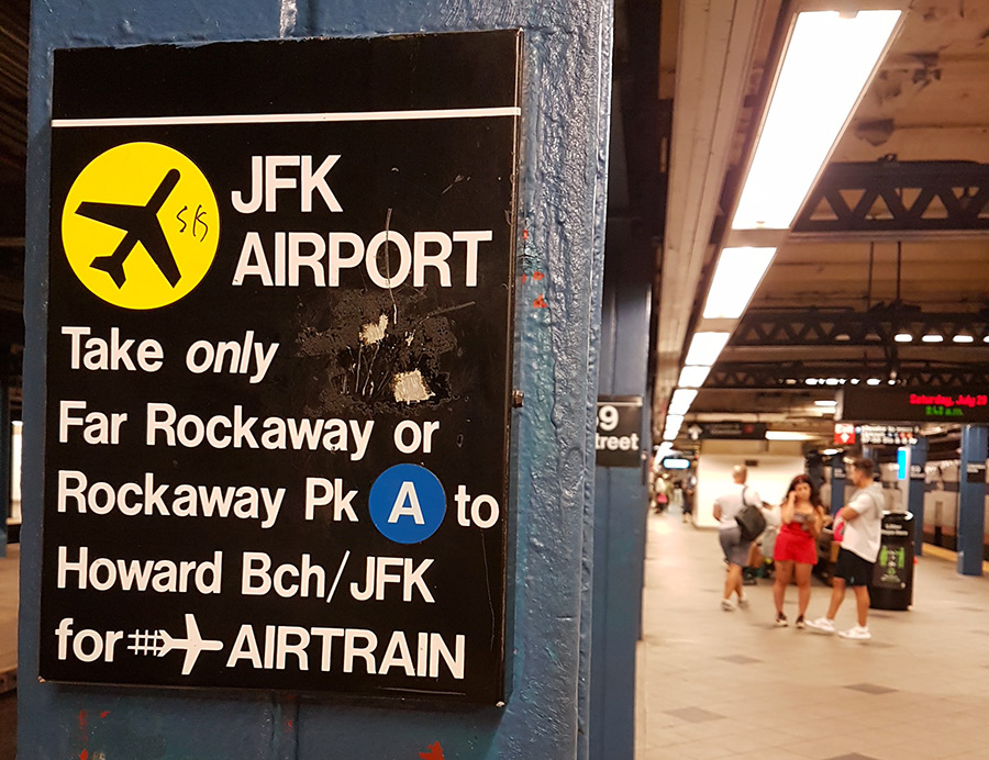 Letrero en una columna del andén de una estación de metro de Nueva York con instrucciones para llegar al Aeropuerto JFK- Foto de Andrea Hoare Madrid