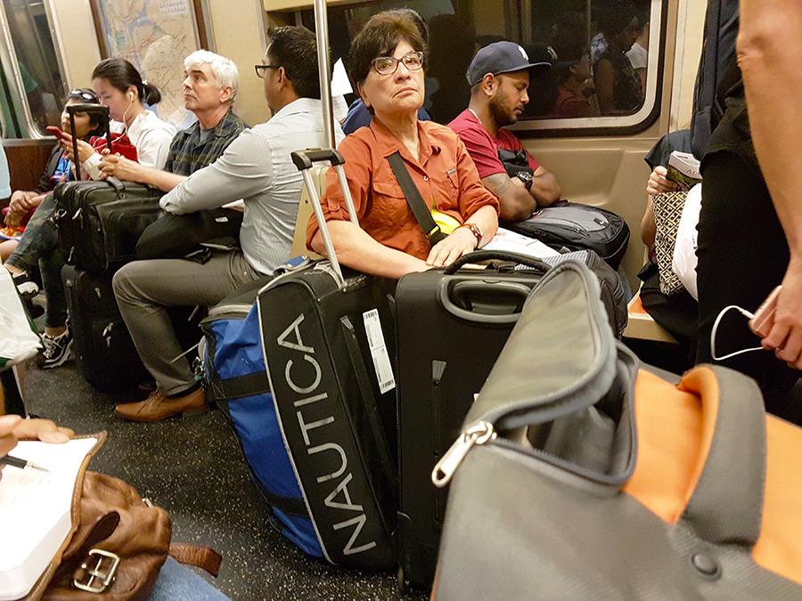 Gente viajando con maletas en el metro de Nueva York - Foto de AHM