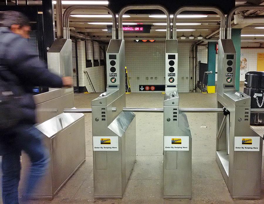 Persona a punto de deslizar la Metrocard en los torniquetes para entrar al andén - Foto de Andrea Hoare Madrid