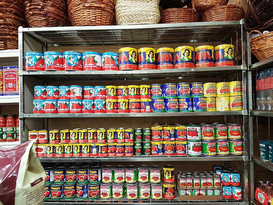 Latas de pomodoro italiano y otros productos importados en un local del Arthur Avenue Retail Market en el Barrio Belmont del Bronx - Foto de Andrea Hoare Madrid