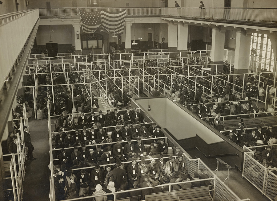 Imagen histórica en blanco y negro de inmigrantes esperando en el Gran Salón de Ellis Island para el control de ingreso de la aduana de Nueva York. Foto de  The New York Public Library en Unsplash disponible en https://unsplash.com/photos/zVFLhNlNj7g