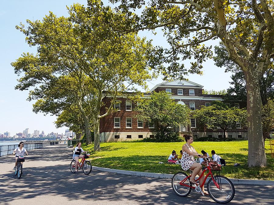 Ciclistas recorriendo la Isla de los Gobernadores al sur de Manhattan, al fondo edificaciones históricas - Foto de Andrea Hoare Madrid