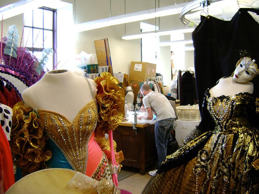 Interior del taller de costura donde hacen el vestuario para los shows del Radio City Music Hall, se ve disfraces listos y a un diseñador trabajando - Foto de Andrea Hoare Madrid