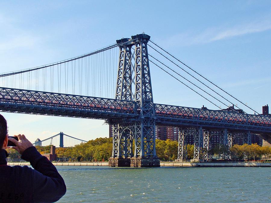 Persona sacando foto al Puente de Williamsburg visto desde el NYC Ferry en el East River - Fotografía de Andrea Hoare Madrid