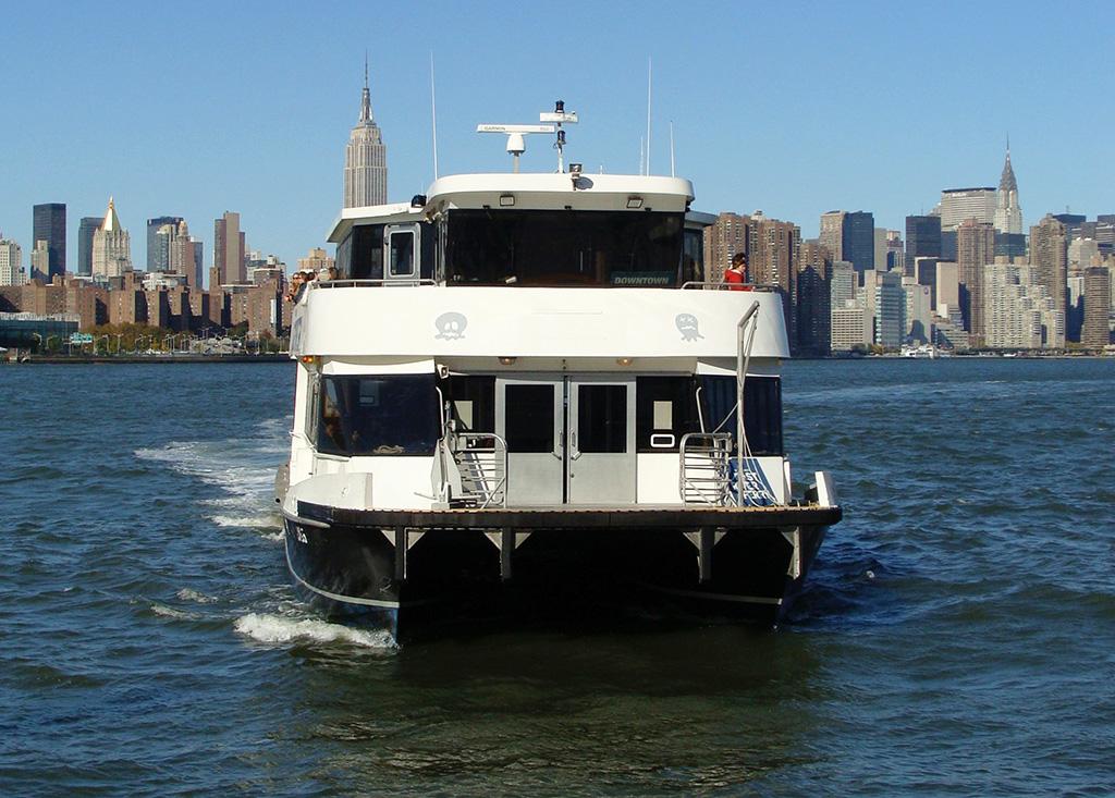Embarcación del NYC Ferry llegando al muelle de Williamsburg, al fondo se ve el Empire State - Foto de AHM