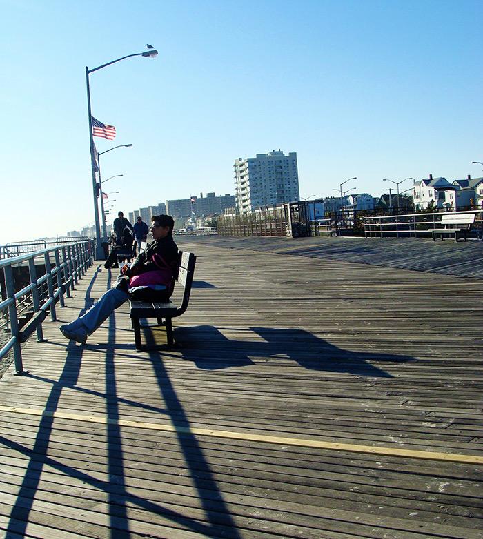 Personas mirando el mar desde las bancas en el boardwalk de Rockaway Beach en Queens - Foto de AHM