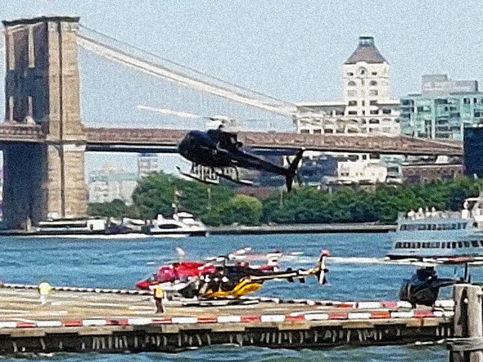 Helicóptero despegando del Downtown Manhattan Heliport en el Pier 6 del East River, al fondo se ve el Puente de Brooklyn - Tours en helicópteros sobre Nueva York - Foto de AHM