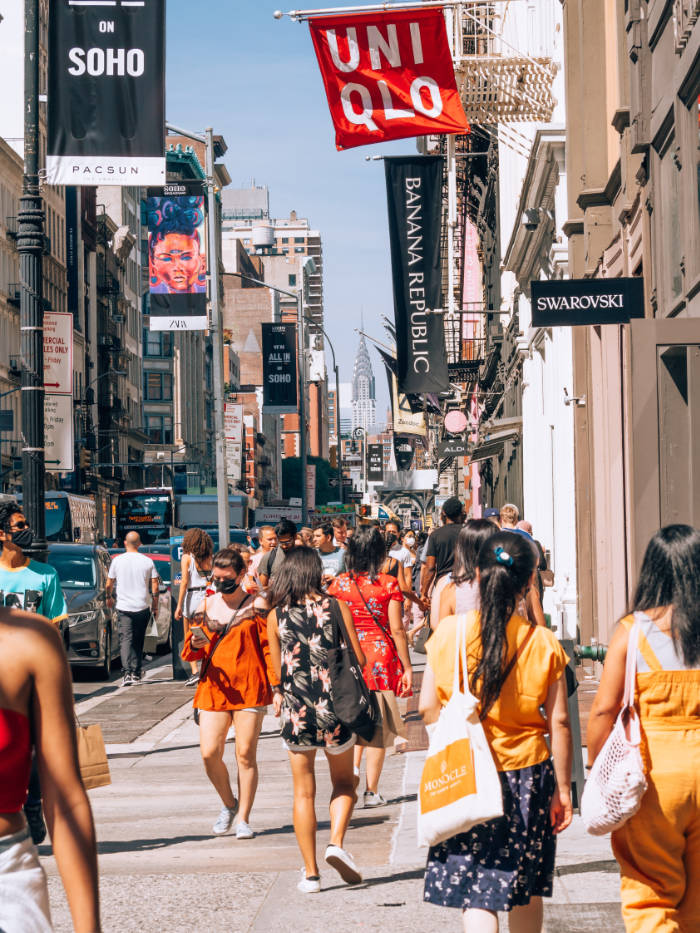 Gente transitando por las calles del SoHo llenas de tiendas y locales comerciales. Foto de Yoav en Unsplash disponible en  https://unsplash.com/photos/jws-3Pb7jps