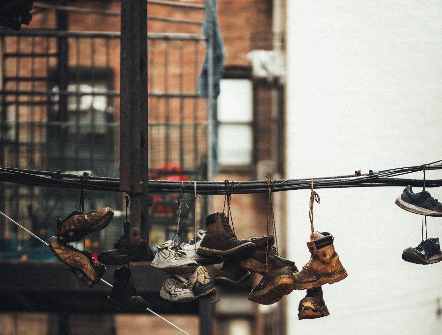 Zapatos colgando en un cable, al fondo los típicos edificios de Bed-Stuy en Brooklyn. Foto de Lerone Pieters en Unsplash, con Licencia Unsplash, disponible en https://unsplash.com/photos/DLrRvTcmadY